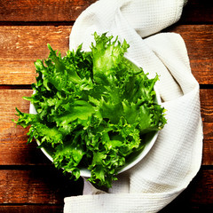 Fresh green salad in a bowl on  wooden background  -  Healthy  R