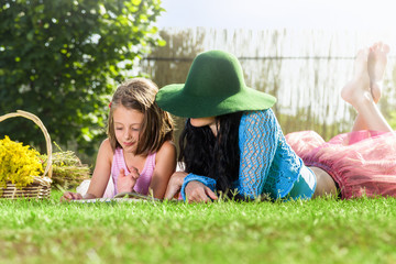 Mother and daughter reading book in the park