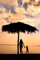 Silhouette of mother and son on the beach