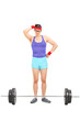 Doubtful male athlete standing behind a barbell