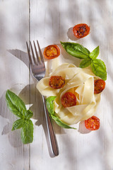 Nest of pasta with basil and tomato