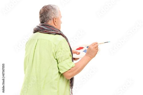 Mature painter holding a paintbrush