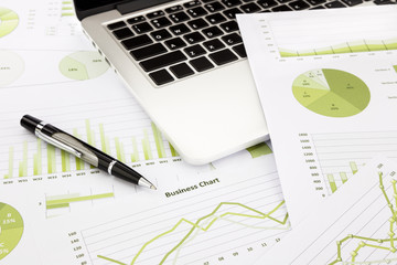 laptop and pen with green business charts, graphs, information a