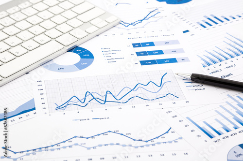 blue graph and chart reports on office table - 67567486