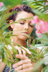 Dreaming young woman portrait with closed eyes between flowers.