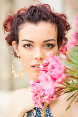 Confident young woman close up portrait with flower.