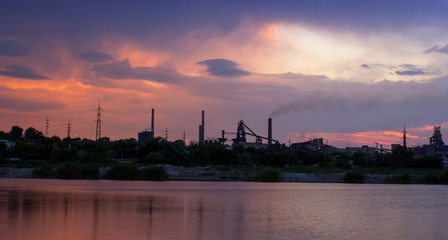 Silhouette of industrial factory at sunset mirror in water