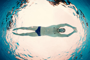 Underwater man inside swimming pool from below. Full body.