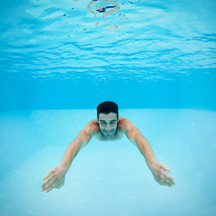 Underwater man inside swimming pool after dipping.