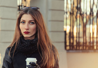 beautiful serious young woman with coffee on the street