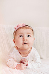 cute little baby girl with pink flower headband looking up and e