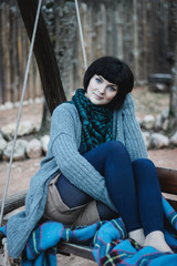 beautiful young woman in knitwear sitting on a swing