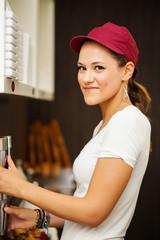 Smiling pretty saleswoman portrait inside ice cream shop.