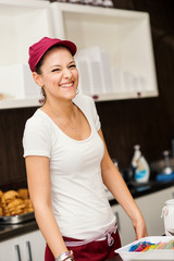 Young laughing saleswoman portrait inside ice cream shop.