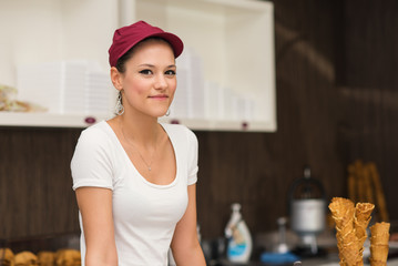 Young smiling saleswoman portrait inside ice cream shop.