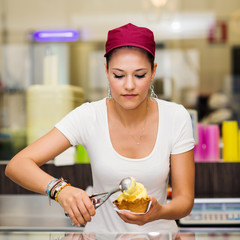 Young pretty saleswoman portrait inside ice cream shop.