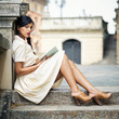 Beautiful brunette woman reading a book outdoors.