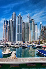 Dubai Marina with boat against skyscrapers in Dubai, UAE