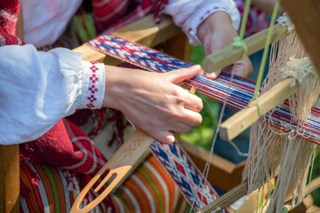 Woman working at the weaving loom.