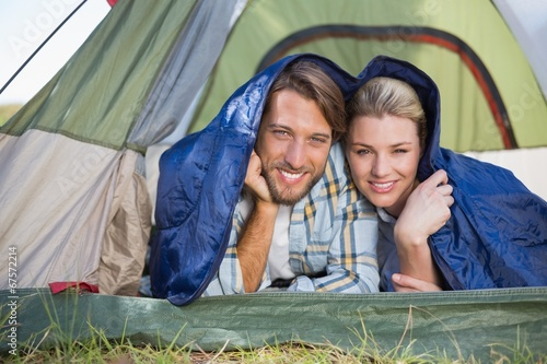canvas print picture Attractive couple lying in their tent smiling at camera