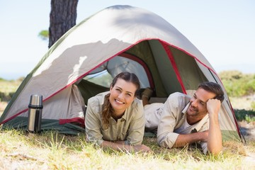 Outdoorsy couple smiling at camera inside their tent