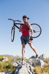 Fit cyclist carrying his bike on rocky terrain