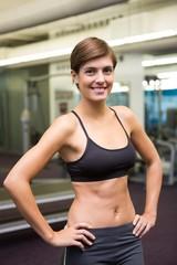 Fit brunette in black sports bra smiling at camera