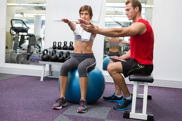Personal trainer with client sitting straight on exercise ball