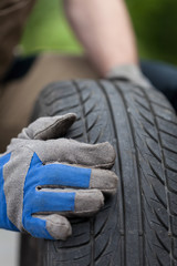 Mechanic hands and car tire