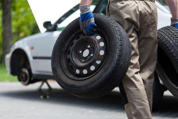 Mechanic holding a two car wheel
