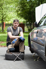Handsome man repairing car outdoors