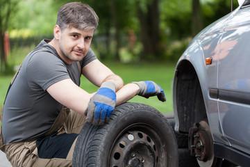 Car mechanic working outdoors
