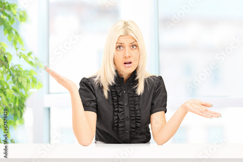 Woman gesturing uncertainty seated at home