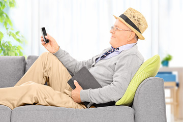 Senior man sending an sms via cell phone at home