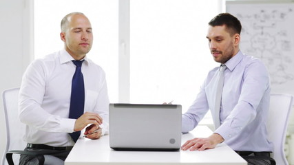 two smiling businessmen with laptop in office