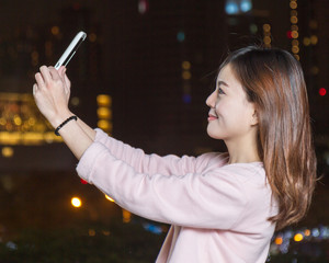 Attractive Asian Woman Taking a Selfie with Cell phone