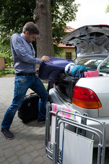 Man pushing luggage into trunk of his car