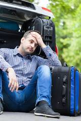 Man having problem with packing luggage into a car