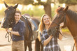 Leinwandbild Motiv Young couple with horses