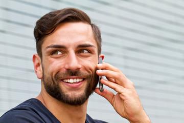 Junger, moderner Mann beim Telefonieren