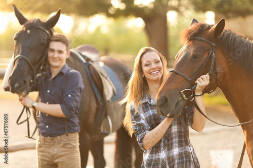Young couple with horses - 67576610