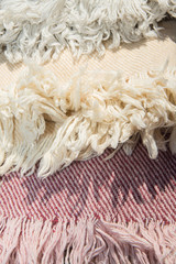 Strip light colour woven  rug surface with fringe close up. Balt