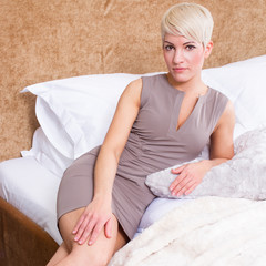 portrait of business woman laying on bed in hotel room