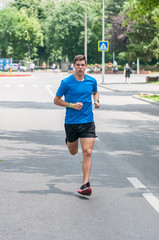 Young athlete training by running on street