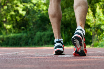 Muscular athlete legs waiting at the starting line on track