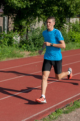 Good looking athlete training on the running track