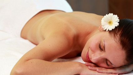 Peaceful brunette lying on massage table smiling at camera
