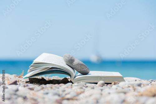Leinwanddruck Bild Book on the beach