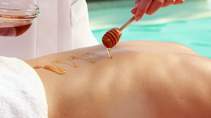 Beauty therapist pouring honey onto womans back