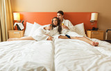 Fototapety Young Couple lying in the bed of a hotel room